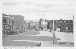 Vintage b/w postcard of historic Riviere-du-Loup (Bas-St-Laurent, Quebec), Commercial Street with classic cars and vintage retail signs