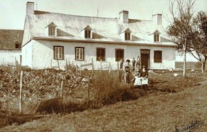 traditional Quebec home with farming family in front yard next to vegetable garden