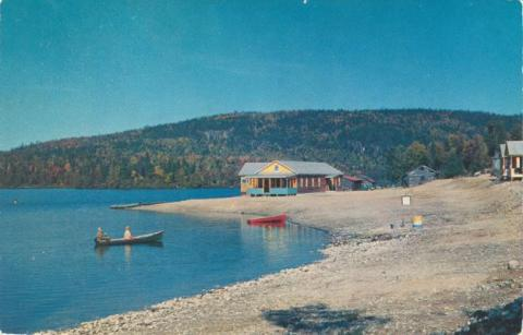 ca. 1950s Vintage canoes on lake and vacation cabins \ traditional canoes