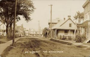 Historical image | St. Liguori (Montcalm, Quebec) - unpaved country road, traditional Quebec wooden houses