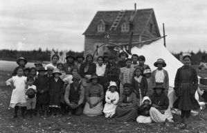 Mingan First Nations, Large Family Grouping | Historic image with building and tent in the background.