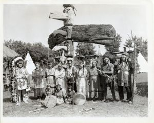 Caughnawaga Kahnawake Group of Mohawk (Iroquois) in traditional garb   1050s   Large group including adults and children in front of totem pole and other First Nations traditional artefacts