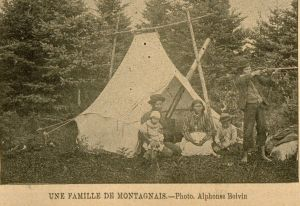 Montagnais family sits in front of tent, young man points a rifle