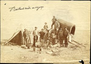 Metis trading family (inc. children) | Western Canada | stands in front of makeshift tent and wagon